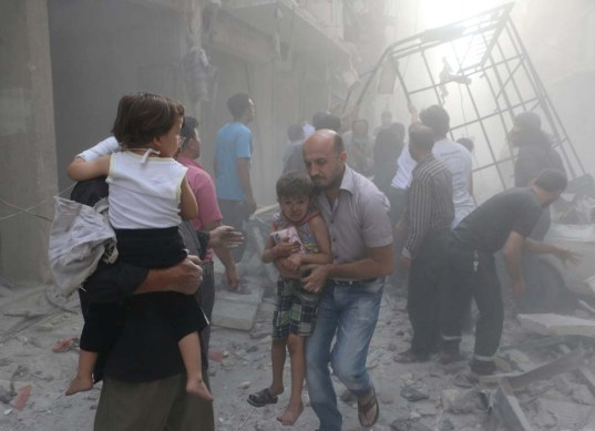 Syrians carry children amid debris following a air strike by government forces in the northern city of Aleppo on July 15, 2014. More than 170,000 people have been killed in the three-year war, one third of them civilians, according to the Syrian Observatory for Human Rights. AFP PHOTO / BARAA AL-HALABI