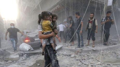un-homme-porte-deux-fillettes-dans-ses-bras-apres-un-bombardement-du-regime-syrien-le-9-juillet-2014-a-alep_5162585